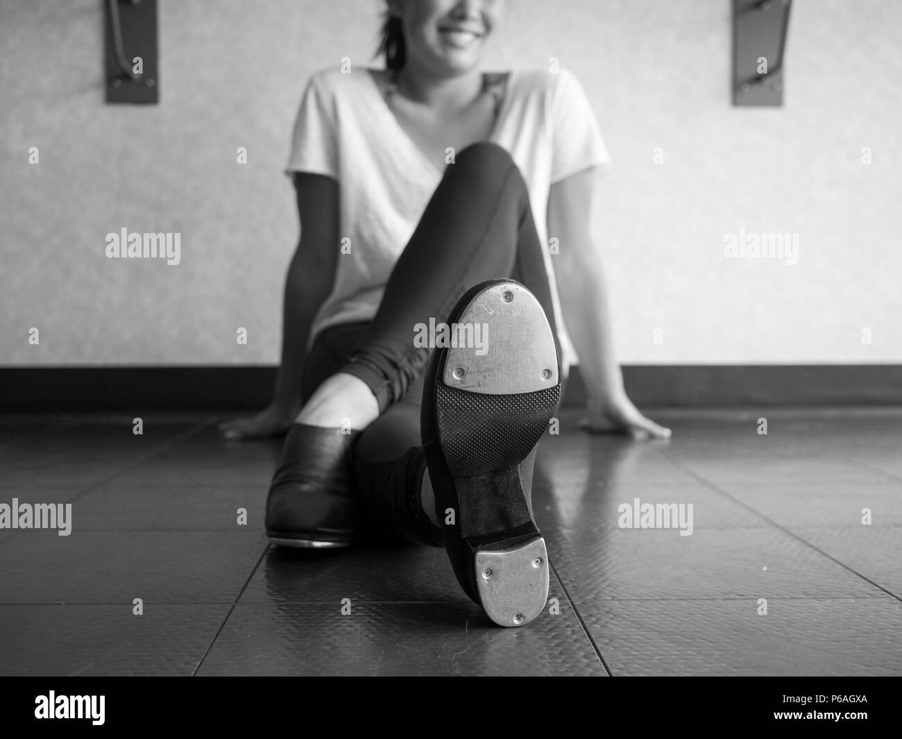 Black and white version of Smiling teenage tap dancer sitting cross legged in dance class relaxing - Stock Image