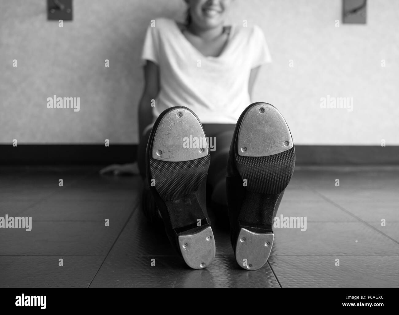 Black and white version of Smiling tap dancer sitting on the dance studio floor in her tap shoes - Stock Image