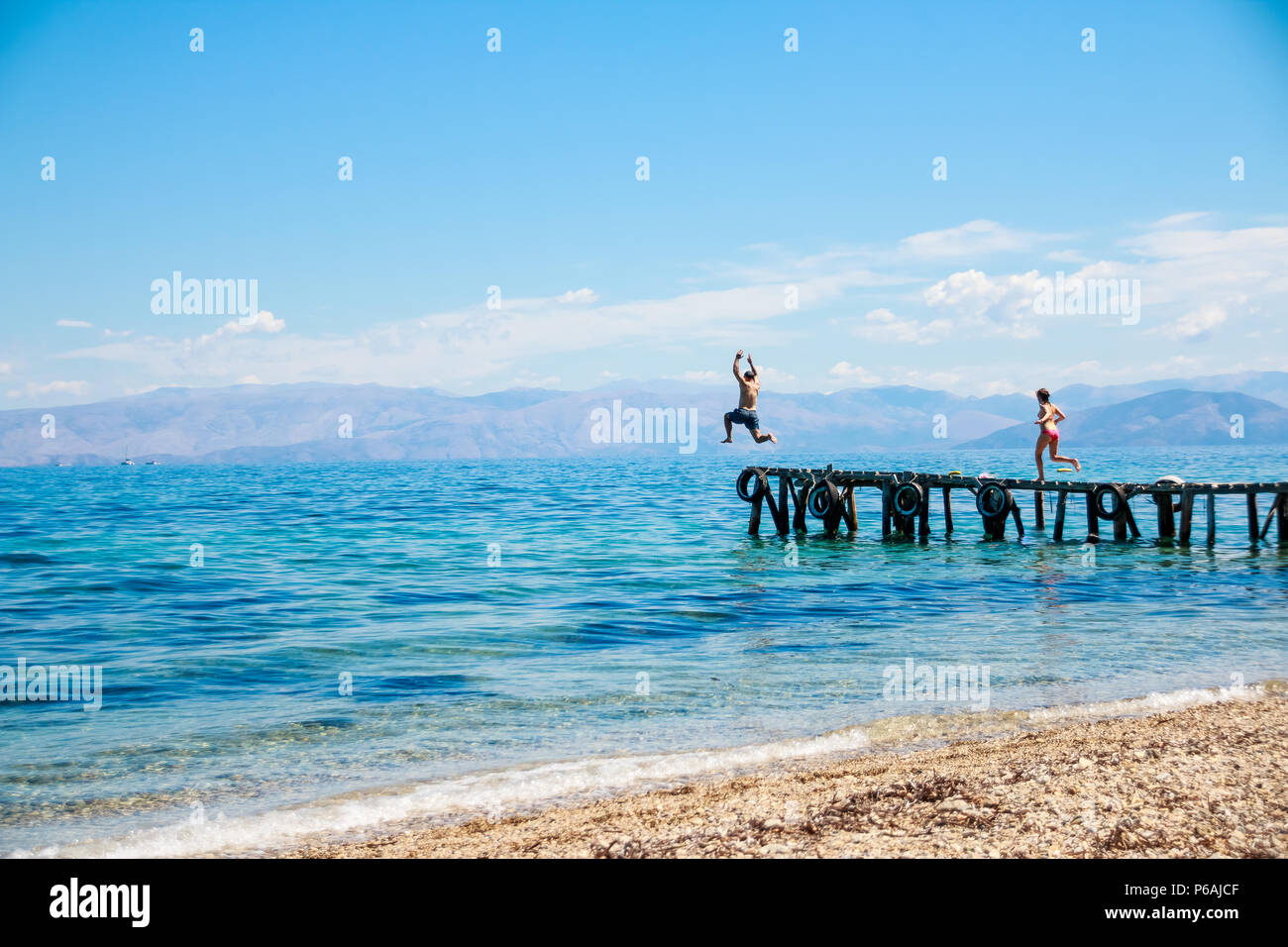 teenagers jumping off the pier into the sea. fun summer vacation.Young man jumps into the blue water from pier. View in motion.Happiness, summer, fun.Copy space Stock Photo
