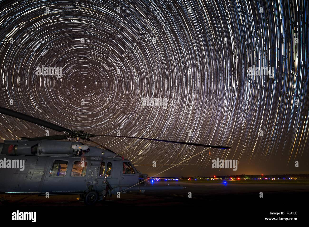 Star light shines on an HH-60G Pave Hawk on the flightline during the Eta Aquarid meteor shower, May 5, 2016, at Moody Air Force Base, Ga. This photo shows the path of the stars as the Earth rotates over the course of two hours. (U.S. Air Force photo by Senior Airman Ryan Callaghan) - Stock Image