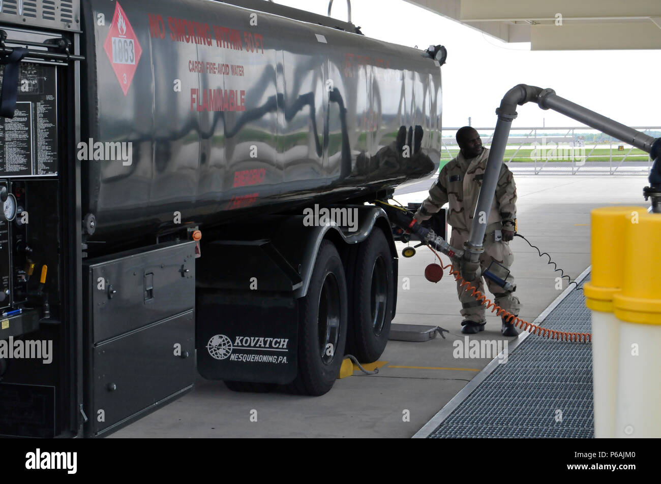 Tech  Sgt  Richard Spencer fills a fuel transportation
