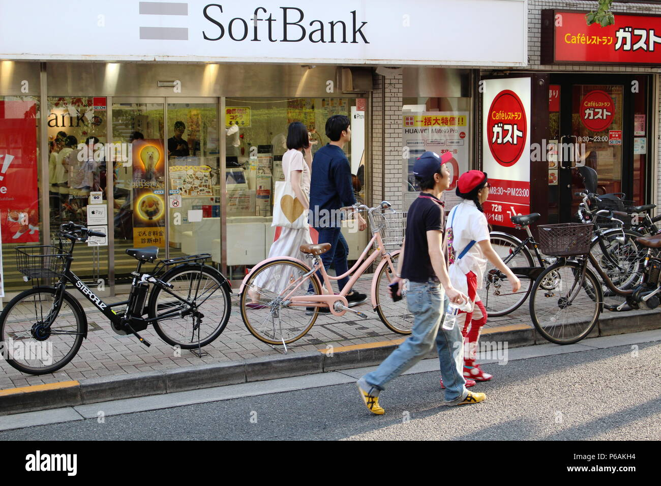 View of a street in the hilly Kagurazaka area with a Softbank branch and a Gusto restaurant. (6/2018) - Stock Image