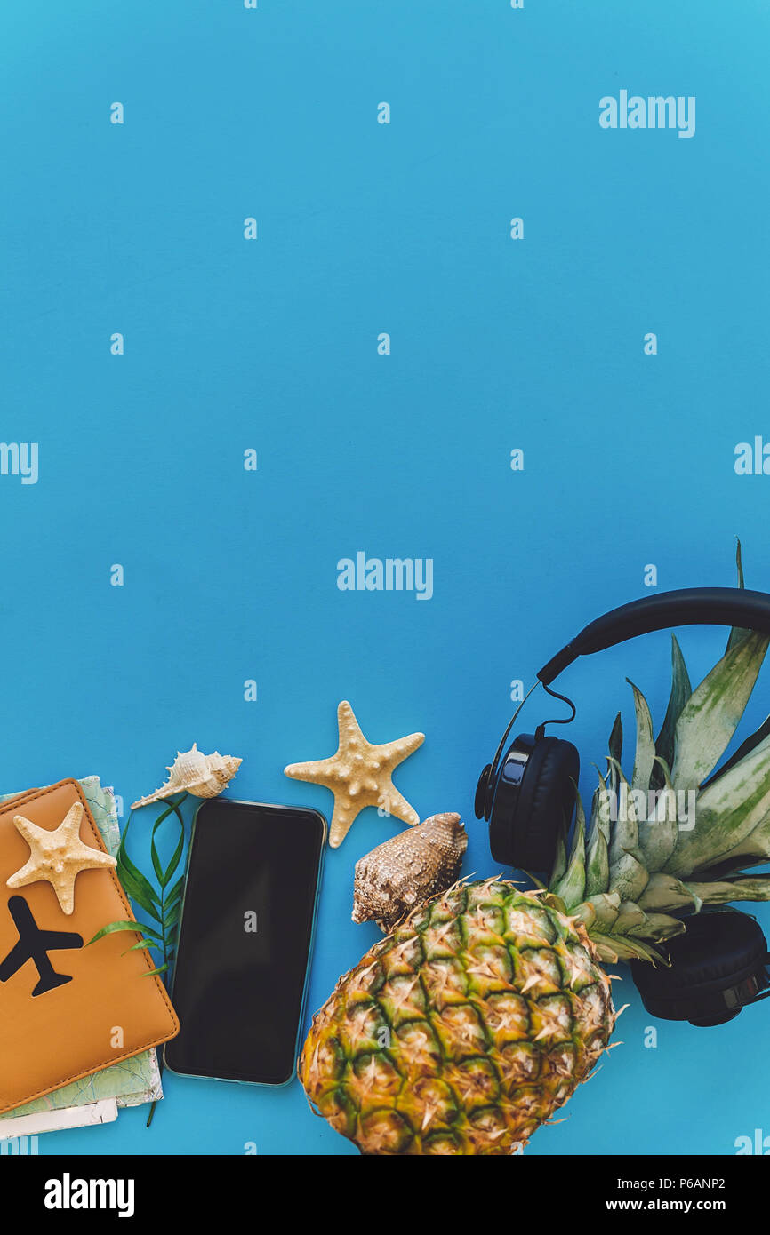 summer vacation and travel flat lay. stylish black phone, passport, sunglasses, map, pineapple with headphones, shells on trendy blue paper. space for Stock Photo