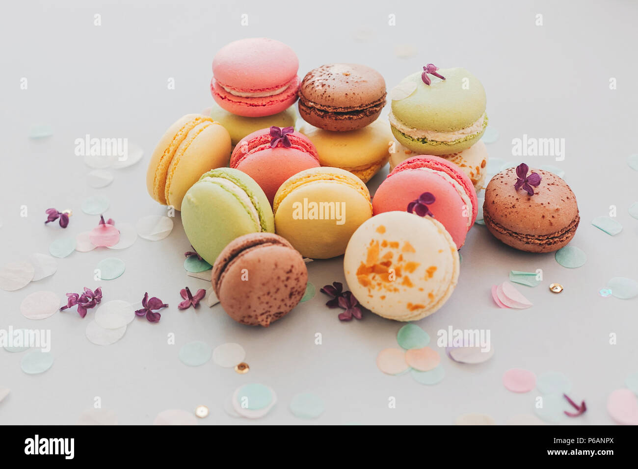 tasty pink, yellow, green and brown macaroons on trendy pastel gray paper with lilac flowers and confetti. space for text. delicious colorful macaroon - Stock Image