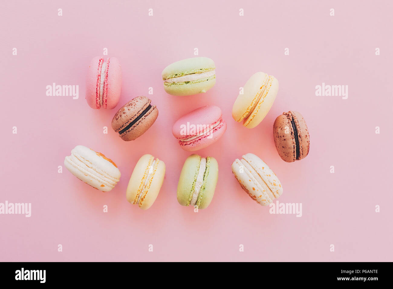 stylish colorful macaroons on trendy pink paper, flat lay. space for text. modern food photography concept. tasty pink, yellow, green, white, brown ma - Stock Image