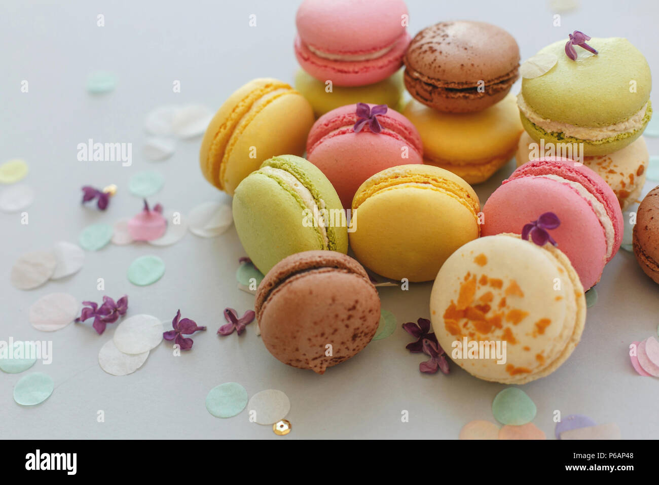 colorful macarons on trendy pastel gray paper with lilac flowers and confetti. tasty pink, yellow, green and brown macaroons. candy bar for party. foo - Stock Image