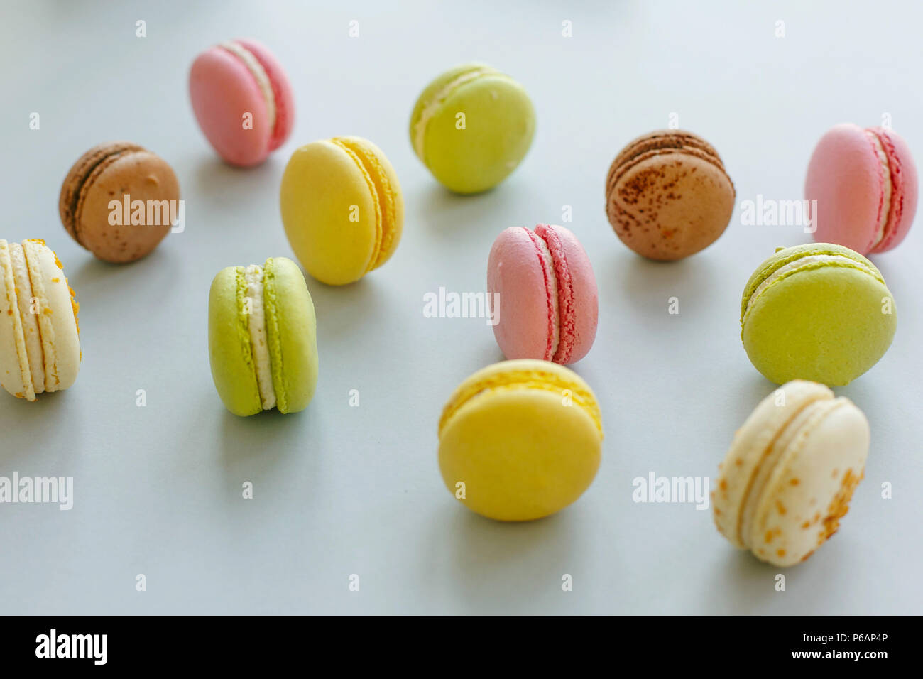 colorful macarons on trendy pastel gray paper. tasty pink, yellow, green and brown macaroons. candy bar for party. instagram food photography. yummy b - Stock Image