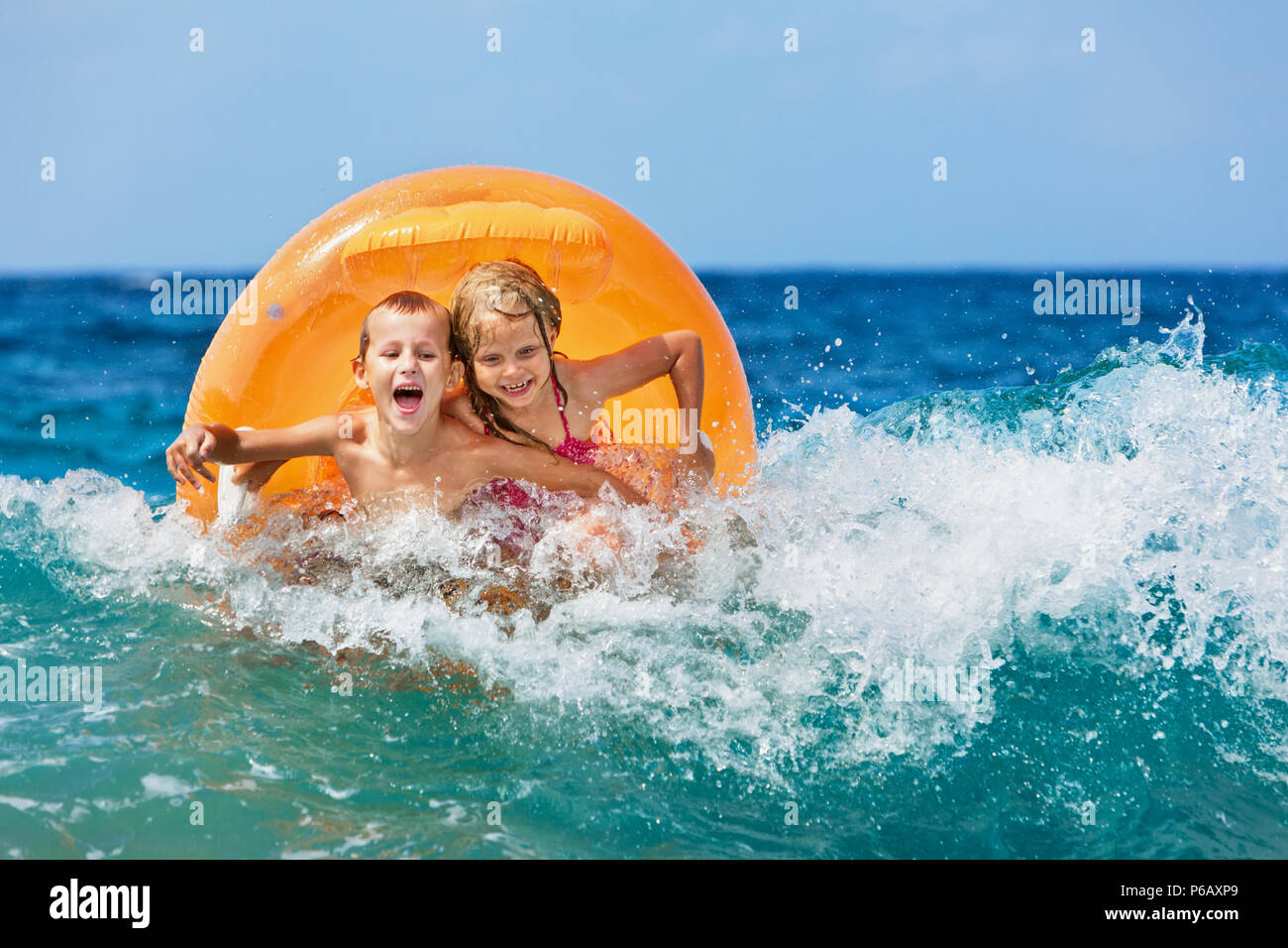 Happy kids have fun in sea surf on beach. Joyful couple of children on inflatable ring ride on wave. Travel lifestyle, swimming activities on holidays - Stock Image