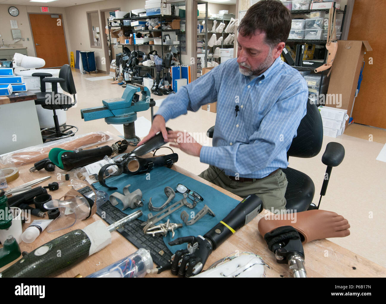David Beachler, a prosthetist, works at his desk inside the prosthetics fabrication room at Walter Reed National Military Medical Center in Bethesda, Md., April 13, 2016. Amputees are consulted before prosthetists design their customized lightweight prosthetics, which weigh less than the actual limb lost. Many of the devices are made or modified in-house. (U.S. Air Force photo/Sean Kimmons) - Stock Image