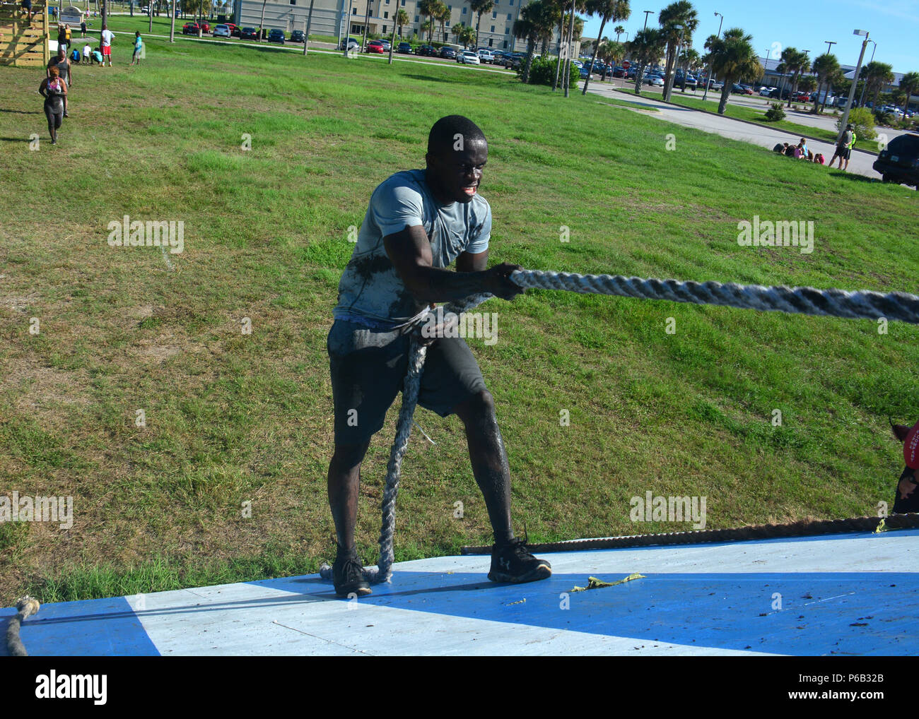MAYPORT, Fla. (Aug. 20, 2016) – Information Systems Technician 1st Class Dinel Mesadieu, assigned to U.S. Naval Forces Southern Command/U.S. 4th Fleet climbs a slanted wall while participating in the Morale, Welfare (MWR) and Recreation Mud Run event. The mud run is an annual event hosted by MWR for service members and their families to participate in with 26 obstacles in the course. (U.S. Navy photo by Mass Communication Specialist 2nd Class Michael Hendricks/Released) - Stock Image