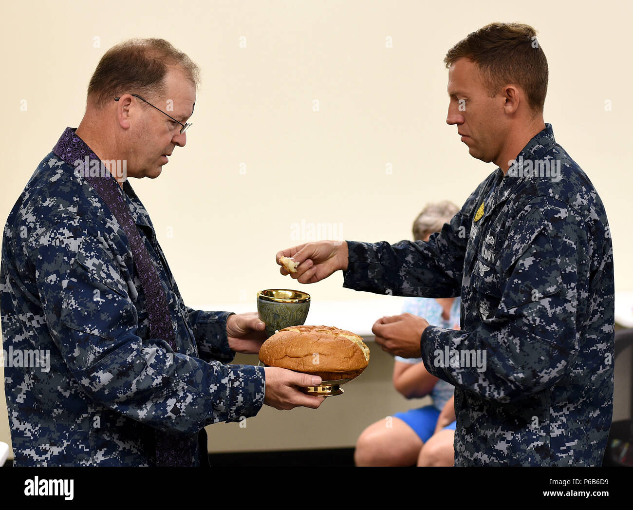 170301-N-SS432-032  BARKING SANDS, Hawaii (March 1, 2017) Command Navy Region Hawaii Chaplain Capt. Brian Haley gives communion to Master at Arms 2nd Class George Weatherby during an Ash Wednesday service at the Pacific Missile Range Facility. (U.S. Navy photo by Mass Communication Specialist 2nd Class Omar Powell/Released) - Stock Image