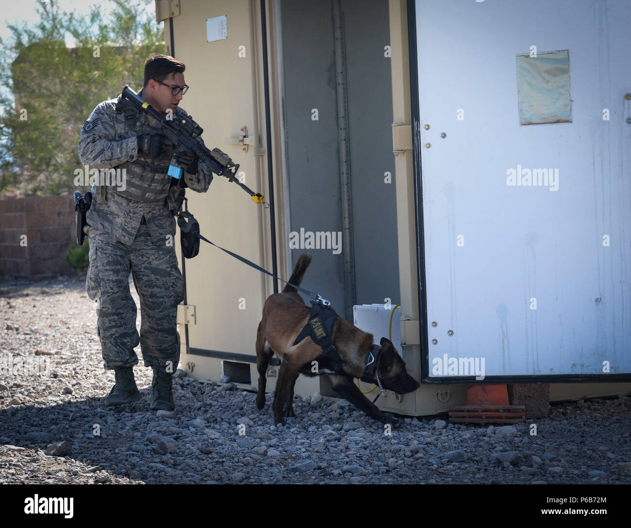 Staff Sgt. Ryne Wilson, a 99th Security Forces Squadron military working dog handler, and his MWD, Seneca, inspect the outside of a building during a training exercise at Nellis Air Force Base, Nev., April 26, 2018. The exercise trained the handlers and their dogs how to detect and seize various explosives and narcotics. (U.S. Air Force photo by Airman Bailee A. Darbasie) Stock Photo