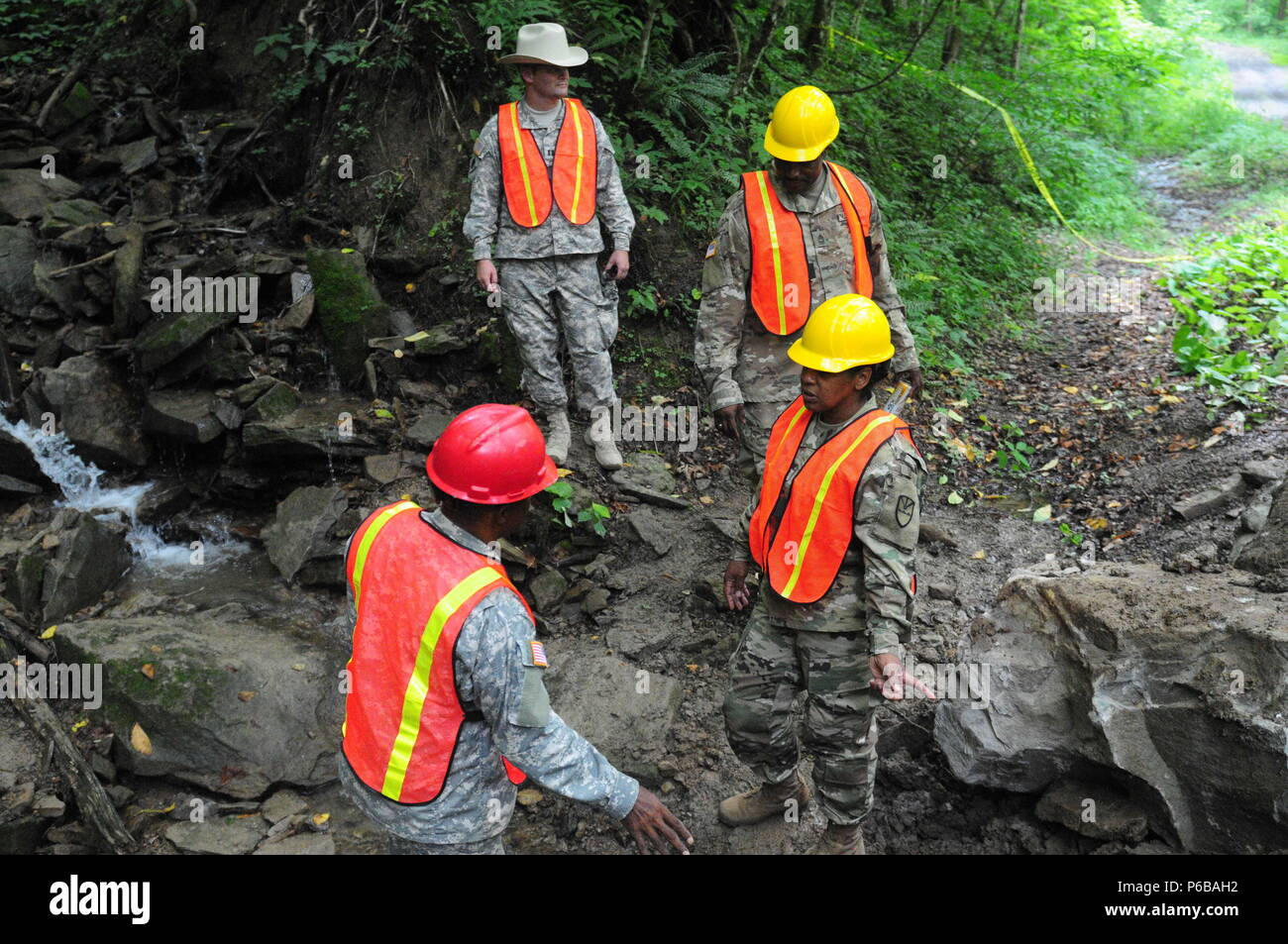 Staff Sgt. Gideon Hurtault, 662nd Engineer Support Company, explains to Battalion Commander, Maj. Nina Clarke-Brewley the work his team did to replace a culvert at Camp Dawson, West Virginia June 21. 104th Troop Command Staff and the Virgin Islands National Guard Chief of Staff Col. Shawn Harris visited the company while on annual training. - Stock Image