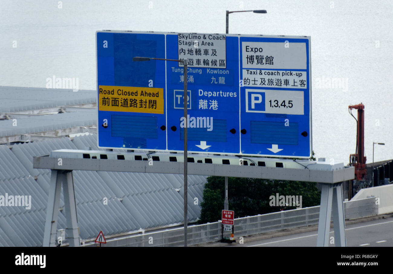 Road sign giving directions to Terminal 2, taxi and coach pick up, Hong Kong Expo in English & Chinese, Chek Lap Kok Airport, Hong Kong International - Stock Image