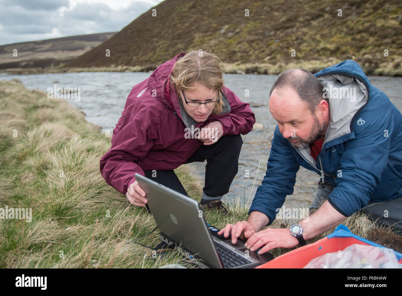 Scientists from the James Hutton institute check water temperature loggers on the River Gairn Scotland - Stock Image