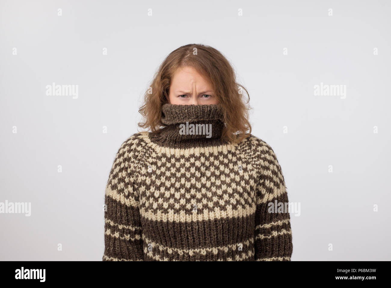 Woman in warm brown sweater hiding her face. Only eyes are seen. She wants to stay anonym. Fear of people and social phobia - Stock Image