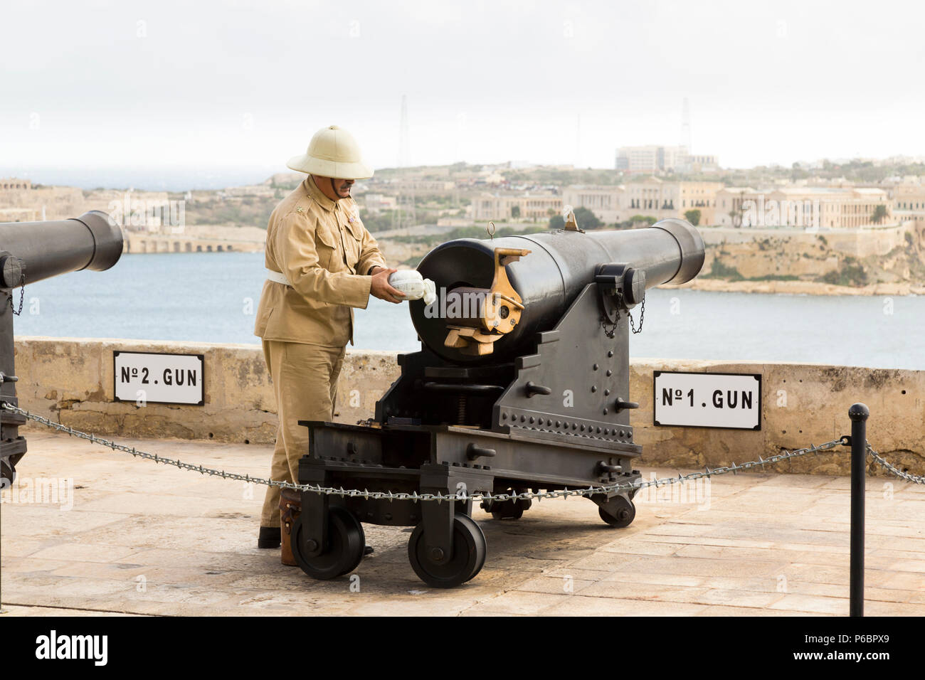 Number 1 Gun of the Saluting Battery artillery battery being prepared / loading powder charge / being loaded to fire the 4pm time signal. Valletta. Malta - Stock Image