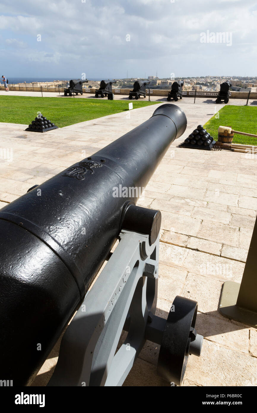 View over cannon / gun towards the Saluting Battery artillery signal guns; one fires 4pm signal every day over the Grand harbour. Valletta, Malta (91 - Stock Image