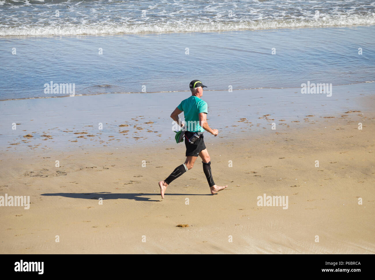 Mature man wearing compression socks/stockings running on beach - Stock Image