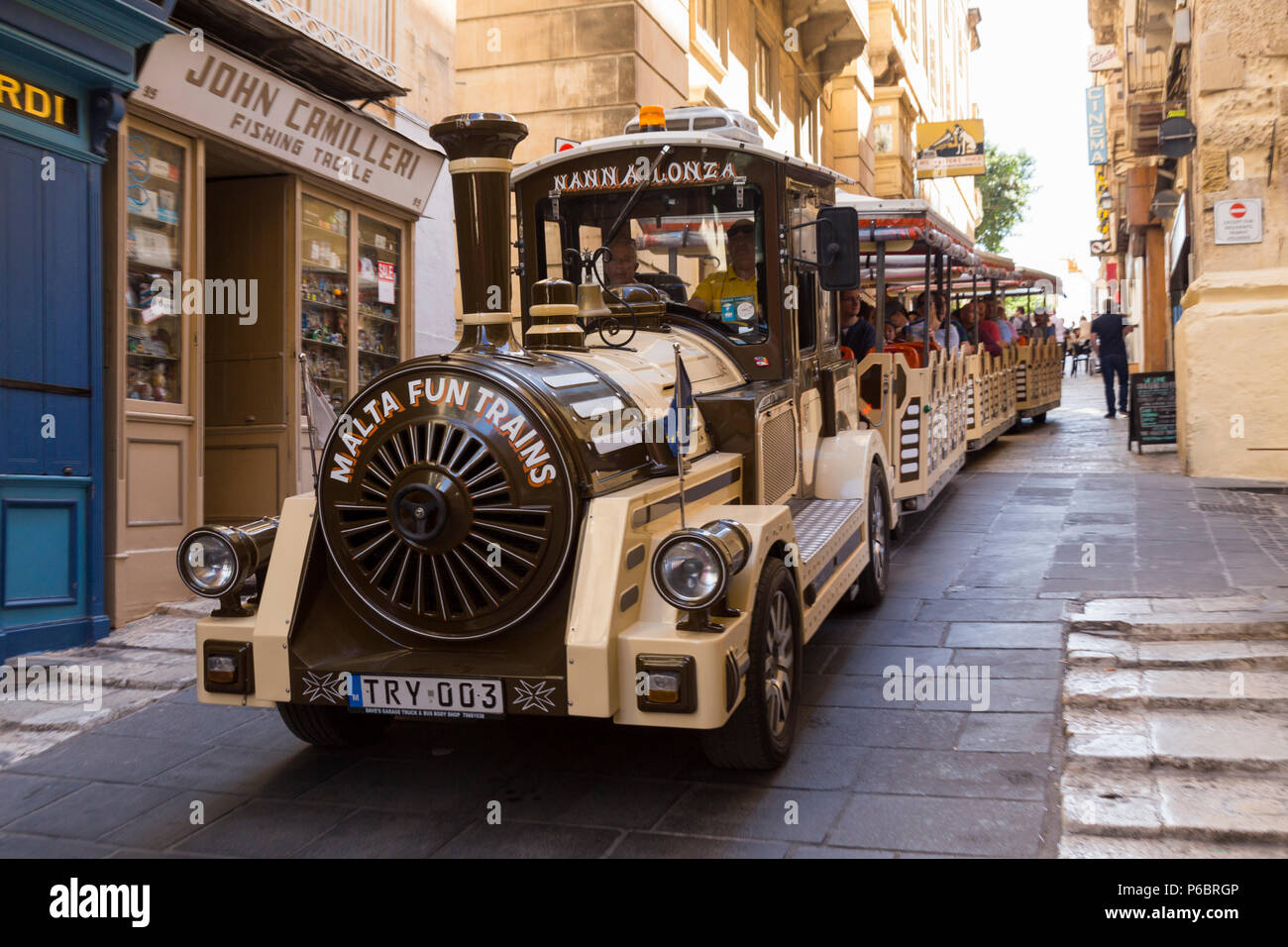 Tourist sightseeing train / trains running in the narrow streets and roads of the historic old city centre of Valletta, Malta. Island of Malta. (91) - Stock Image
