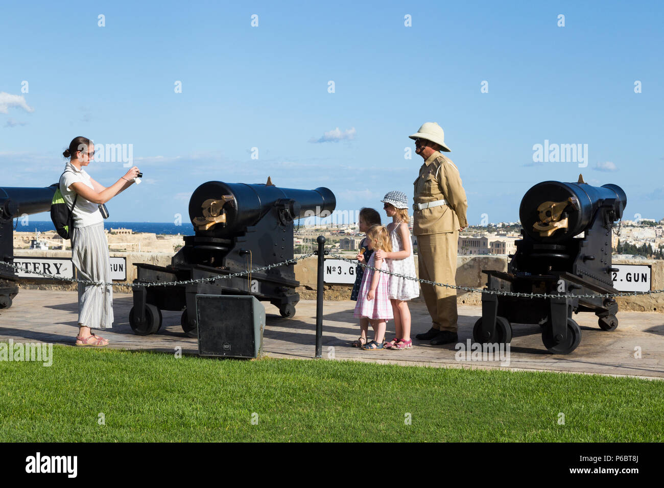 Family pose for photographs beside Number 2 Gun of the Saluting Battery as it is being prepared to fire the 4pm time signal. The Saluting Battery is an artillery battery in Valletta, Malta. - Stock Image