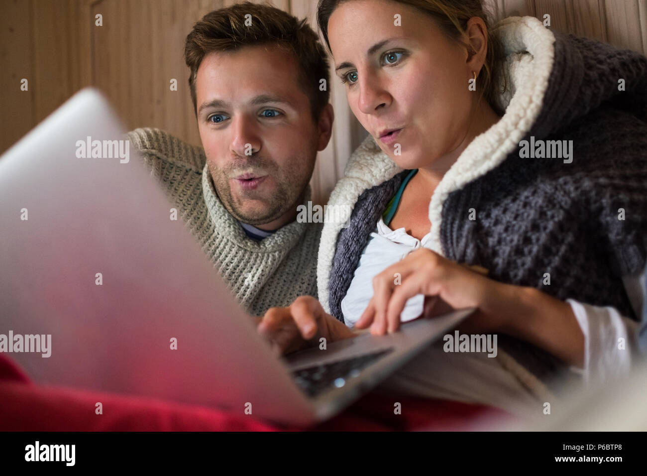 Happy european family making shopping in internet using laptop. Man and woman are happy and smiling getting news form friends speaking with app. Conce - Stock Image
