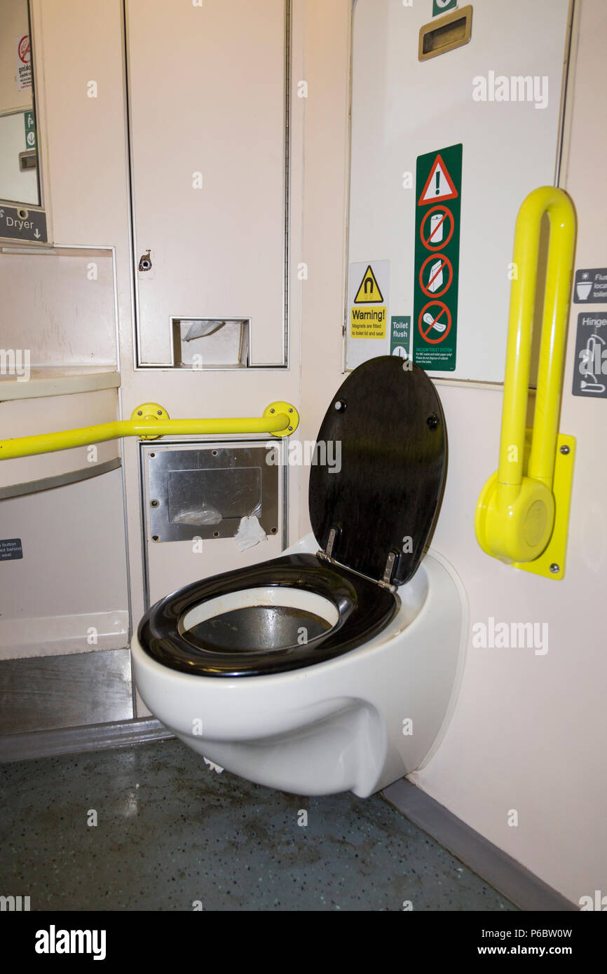 Toilet / lavatory – with wet floor and which is used & a little dirty – with disabled access and bars, & basin sink on UK train near SW London. UK. - Stock Image