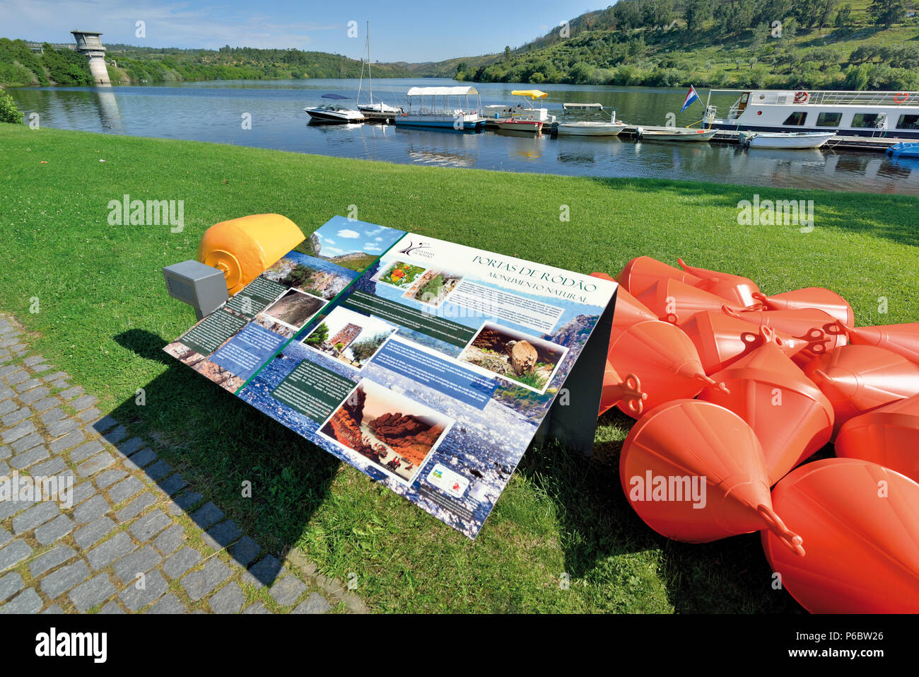 Colorful placard and view to riverboats anchoring at a small dock - Stock Image