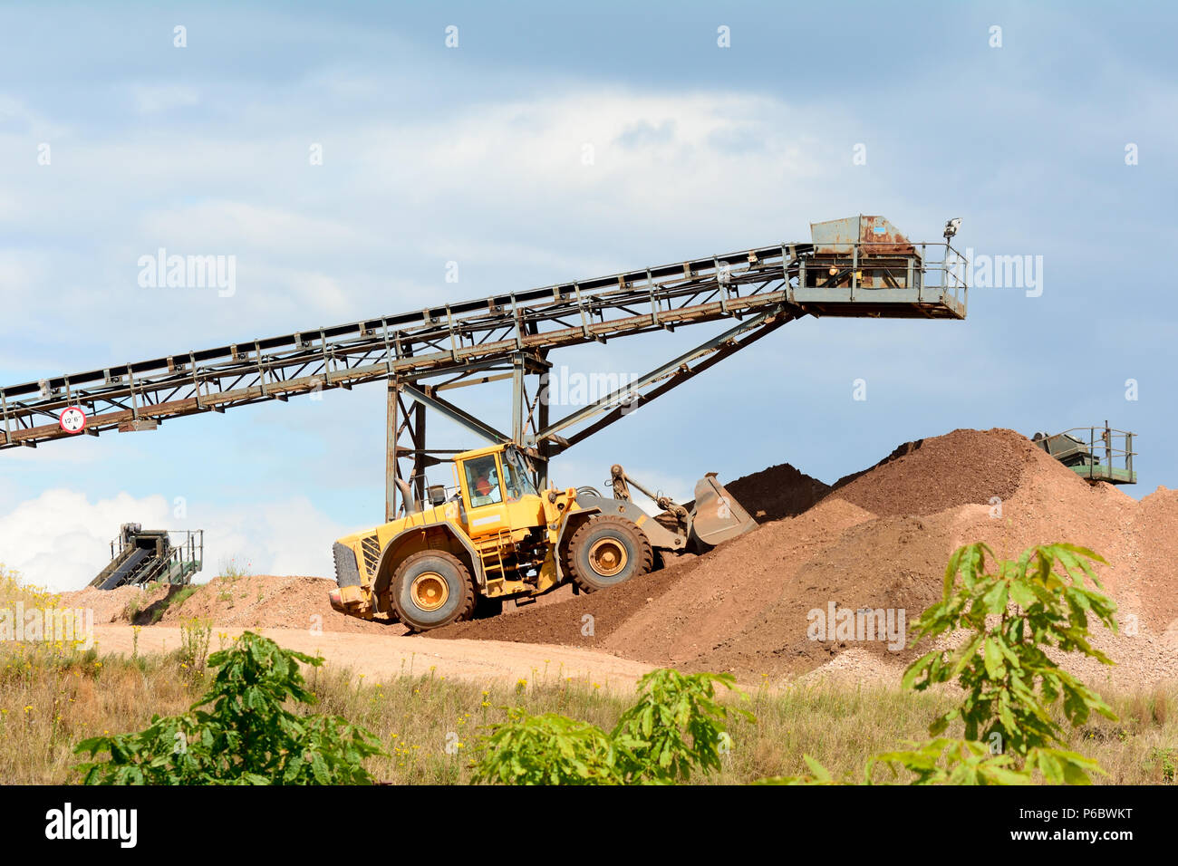 Excavator moving piles of soil into huge mounds from end of