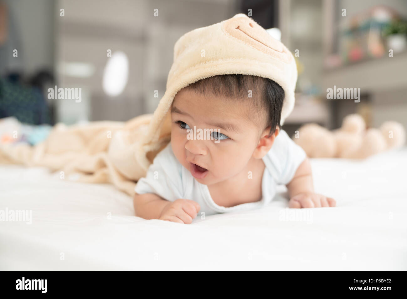 Portrait of a crawling baby on the bed in her room, Adorable baby boy in white sunny bedroom, Newborn child relaxing in bed, Nursery for young childre - Stock Image