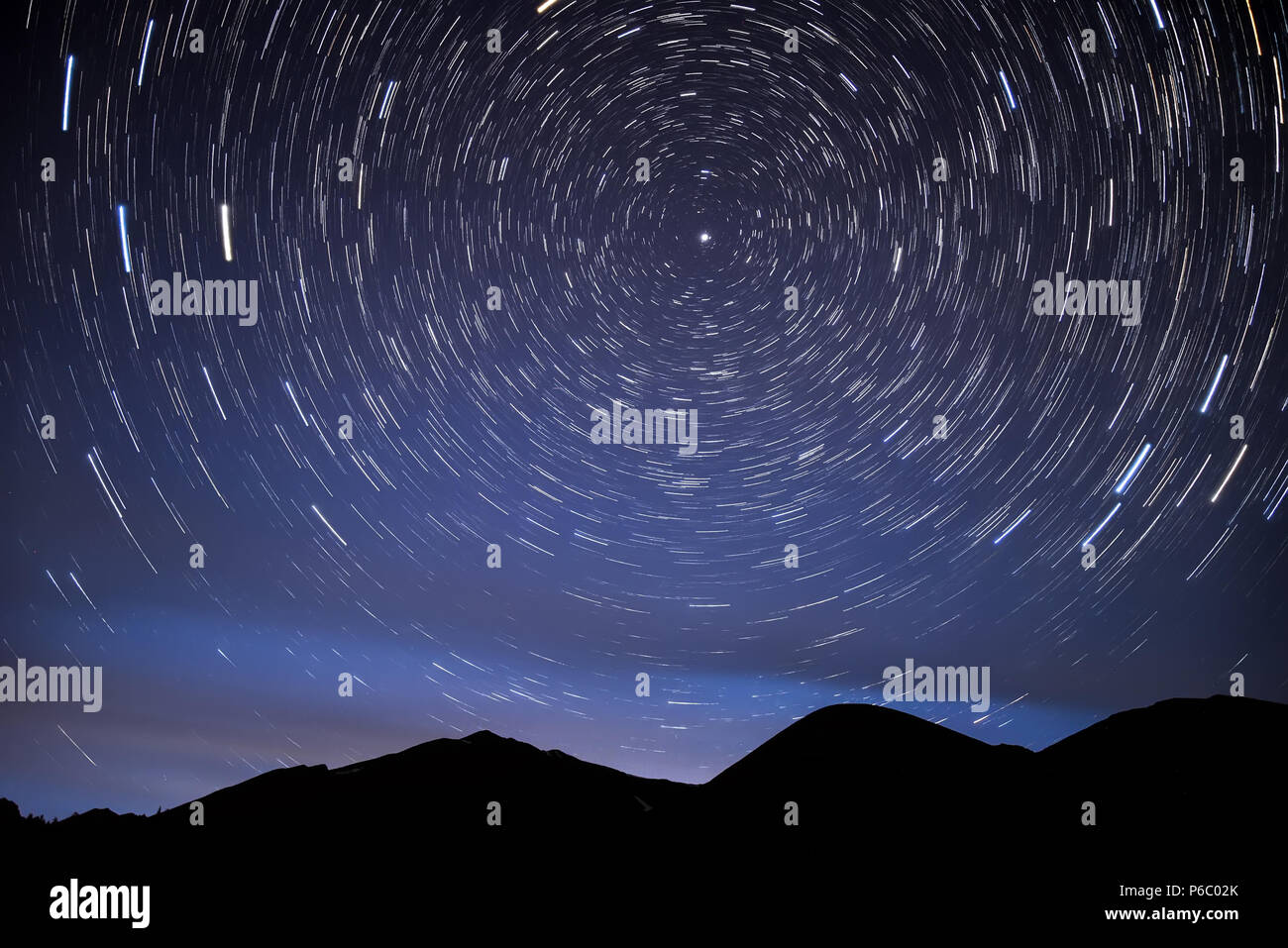Bright Traces Of Stars Revolving Around The Polar Star In Form Circular Tracks And Glow Night Sky Against Background Mountai