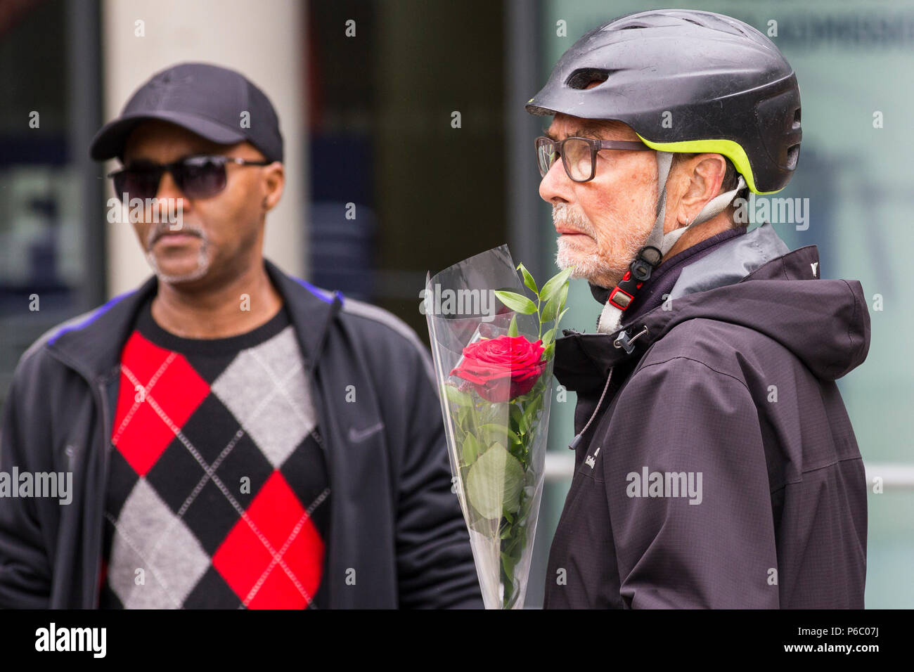 The first anniversary of the 24-storey Grenfell Tower block of public housing flats fire which claimed 72 lives. Man wearing cycling helmet with a red rose, paying his respects at a memorial service  near the tower block.  South Kensington, London, UK, 14th June 2018. - Stock Image