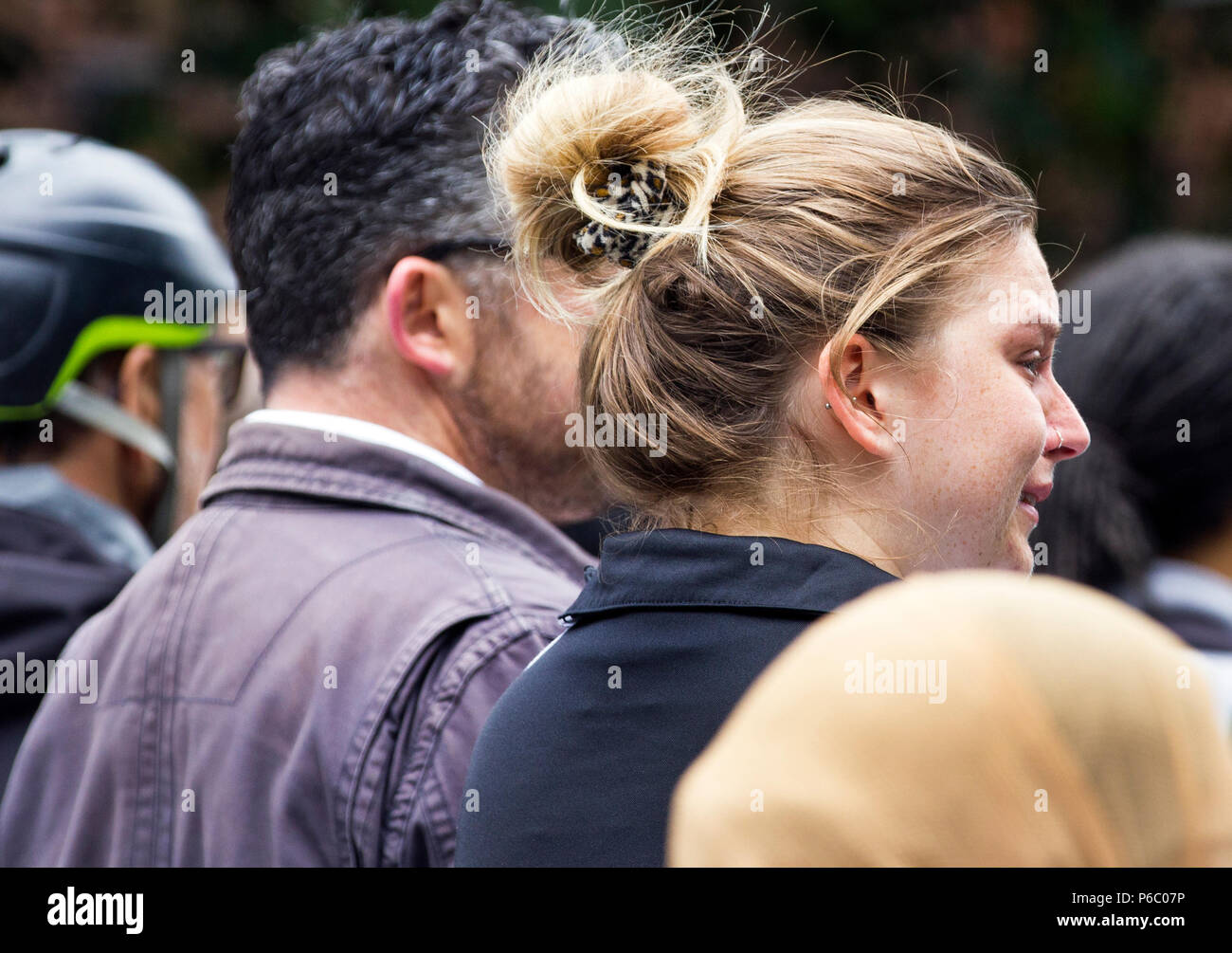 The first anniversary of the 24-storey Grenfell Tower block of public housing flats fire which claimed 72 lives. Young woman crying during the one year memorial service for the victims of the Grenfell tower fire, South Kensington, London, UK, 14th June 2018. - Stock Image