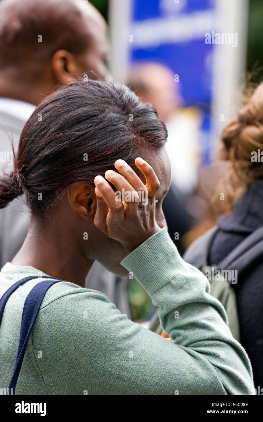 The first anniversary of the 24-storey Grenfell Tower block of public housing flats fire which claimed 72 lives. Young woman wipes away tears during the one year memorial service for the victims of the Grenfell tower fire, South Kensington, London, UK, 14th June 2018. - Stock Image