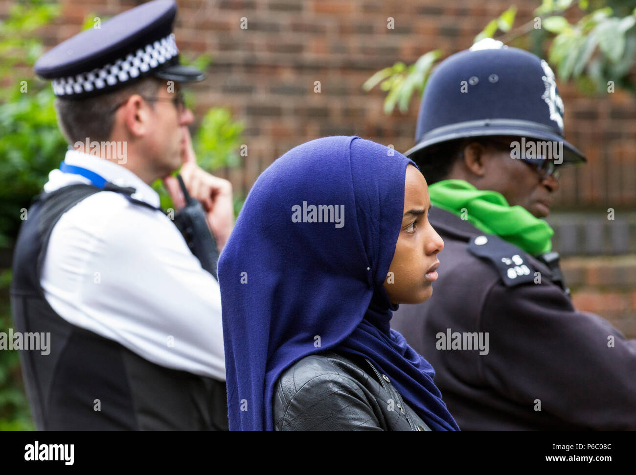 The first anniversary of the 24-storey Grenfell Tower block of public housing flats fire which claimed 72 lives. Young female listening during the public memorial service, standing by two policemen, South Kensington, London, UK, 14th June 2018. - Stock Image