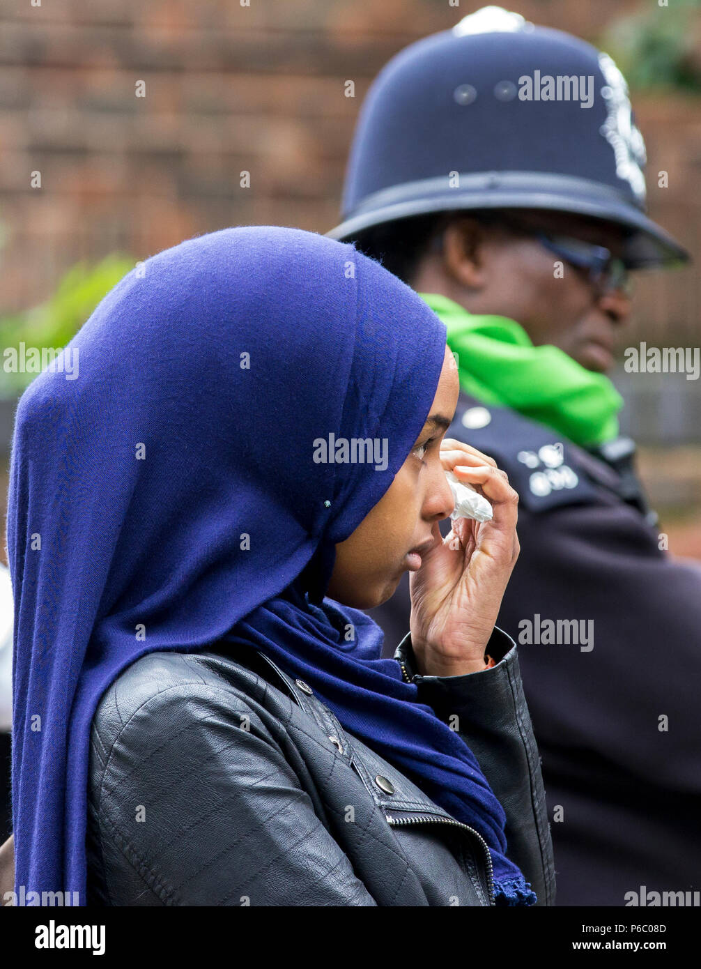 The first anniversary of the 24-storey Grenfell Tower block of public housing flats fire which claimed 72 lives. Young female wipes tears away during the public memorial service, South Kensington, London, UK, 14th June 2018. - Stock Image