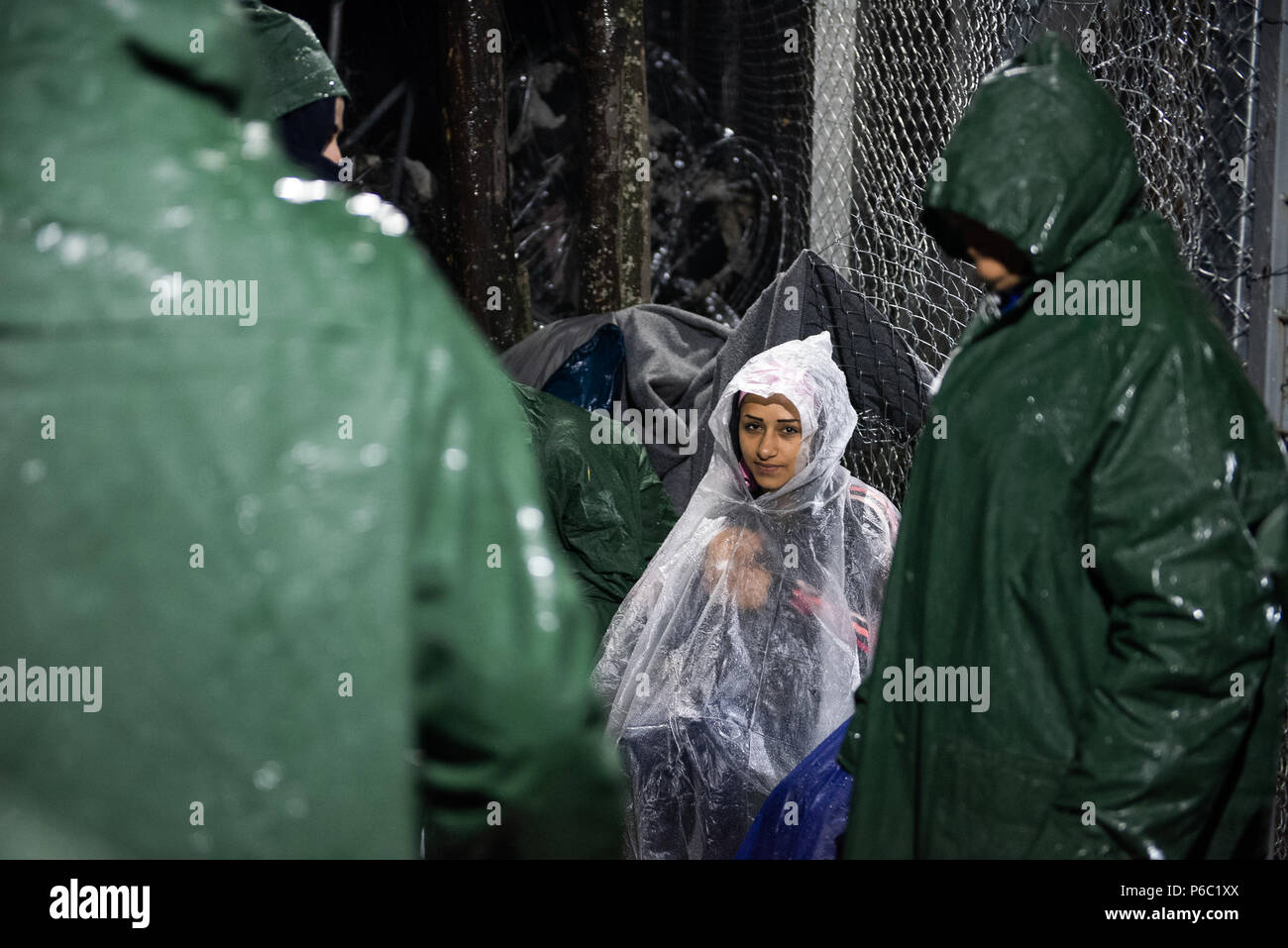 People wearing plastic ponchos sit under the rain as they wait at the makeshift refugee camp  of the Greek-Macedonian border near the Greek village of - Stock Image