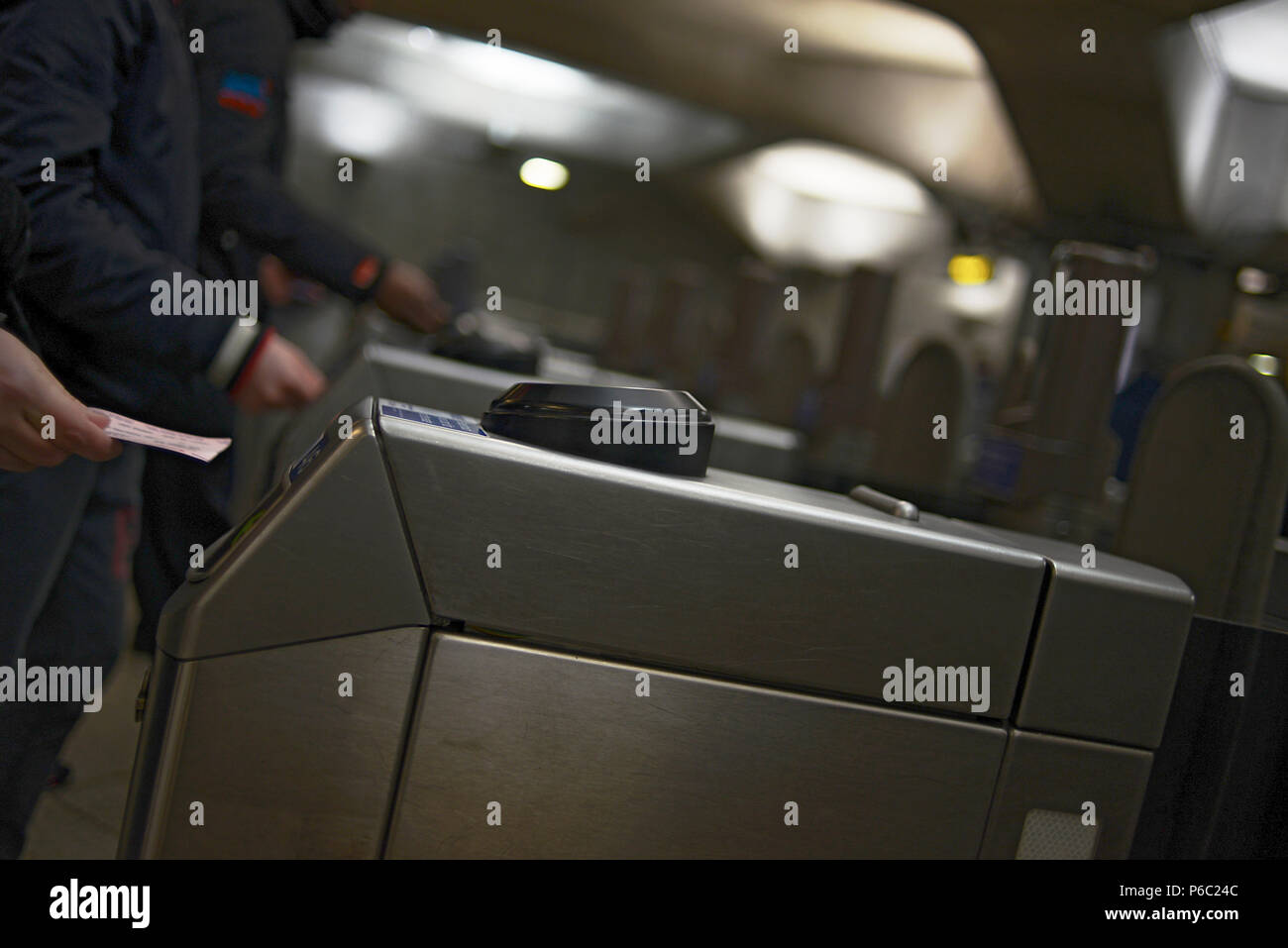 Close up of person tapping in their travel card to enter the turnstyle at the London Underground - Stock Image