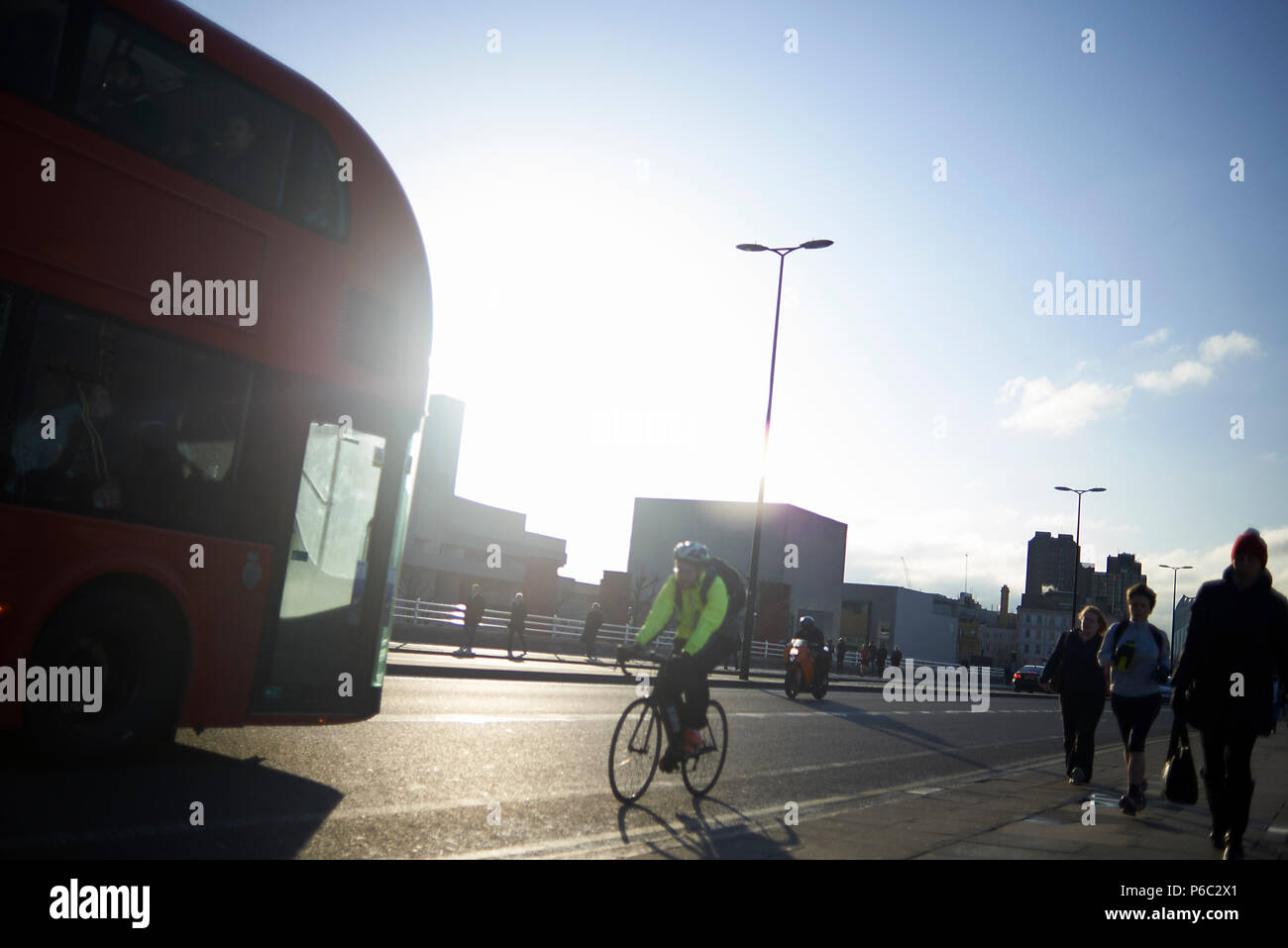 Commuters crossing the bridge over the river Thames in early morning sunshine - Stock Image