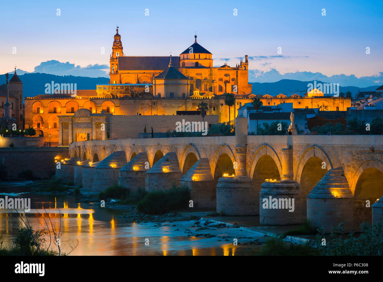 Andalucia Spain architecture, view at night across the Roman bridge on the Rio Guadalquivir towards the Cathedral and La Mezquita in Cordoba, Spain. - Stock Image