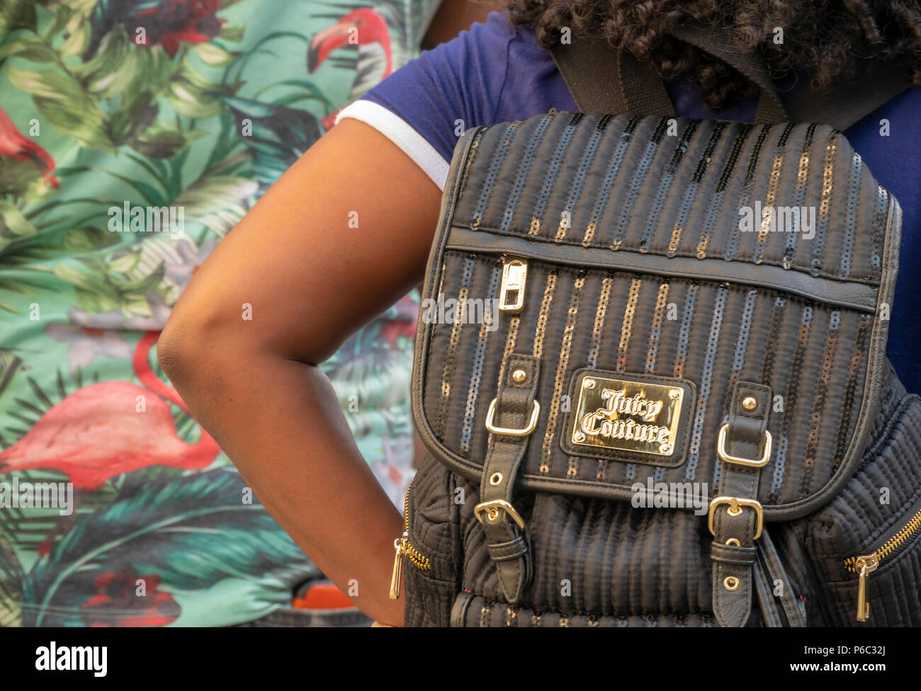 A teen with her Juicy Couture backpack on a street in New York on Saturday, June 16, 2018. Primarily associated with velour track suits, Juicy Couture was sold to Authentic Brands Group in 2013 by its previous owner Fifth & Pacific Inc. (Liz Claiborne) which proceeded to close all of its domestic stores. The brand is till available via the Kohl's department store chain. © Richard B. Levine) - Stock Image