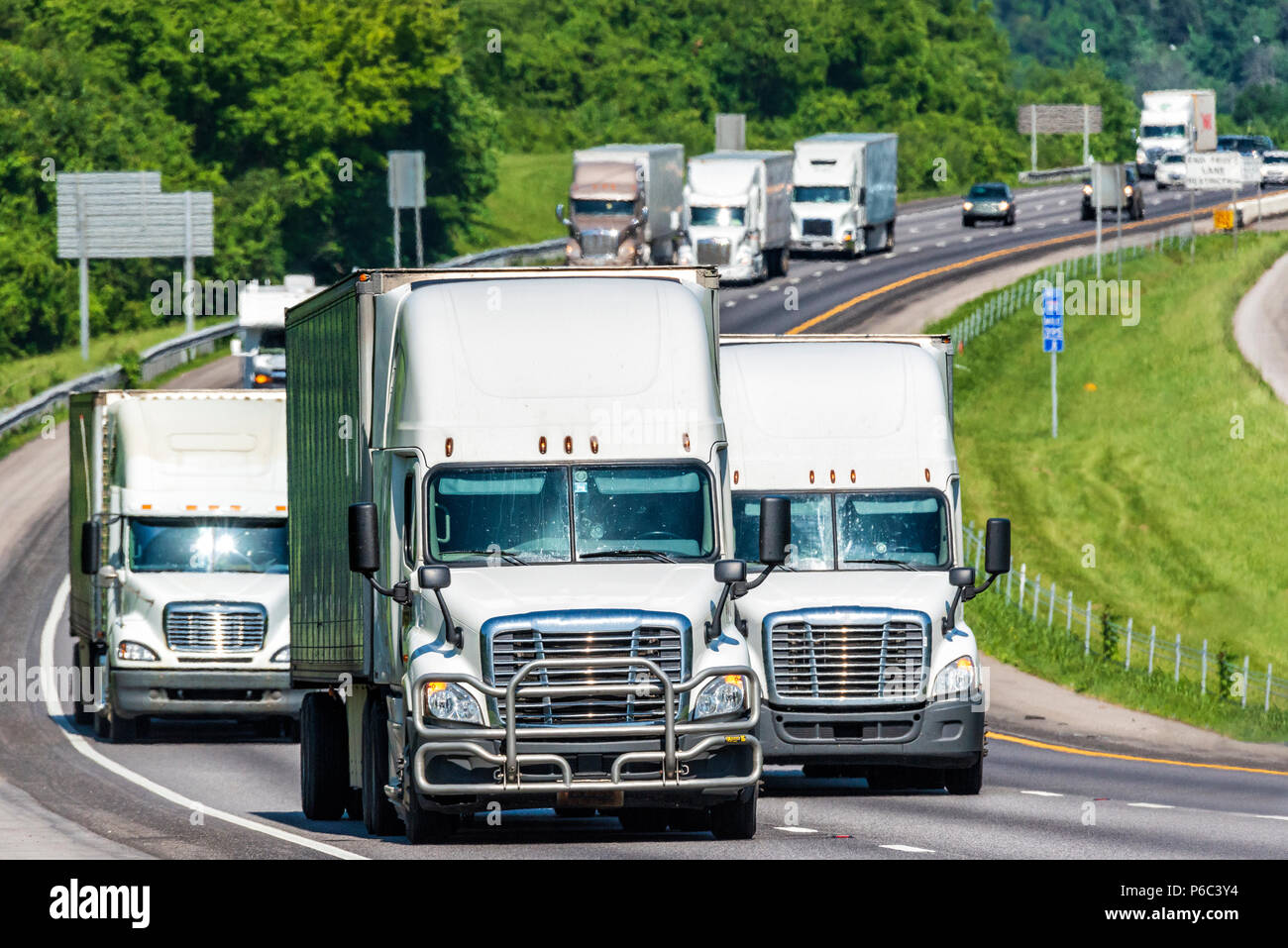 A constant line of heavy trucks move down a busy interstate.  Note: All logos and identifying marks have been removed from all vehicles.  Image was cr - Stock Image