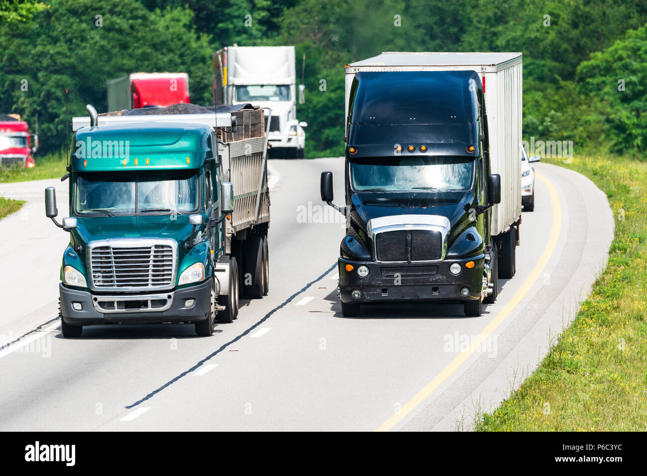 A line of semis travel a Tennessee interstate. Note: All logos and identifying marks have been removed from all vehicles.  Image was created on hot da - Stock Image