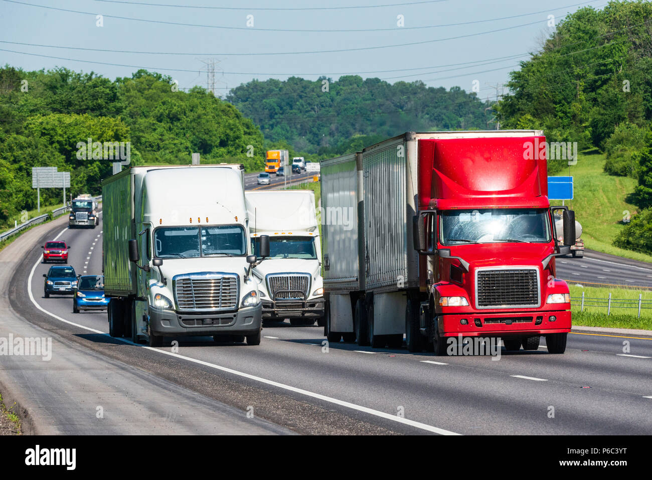 Tractor-trailer trucks lead traffic down the highway. Note: All logos and identifying marks have been removed from all vehicles.  Image was created on - Stock Image
