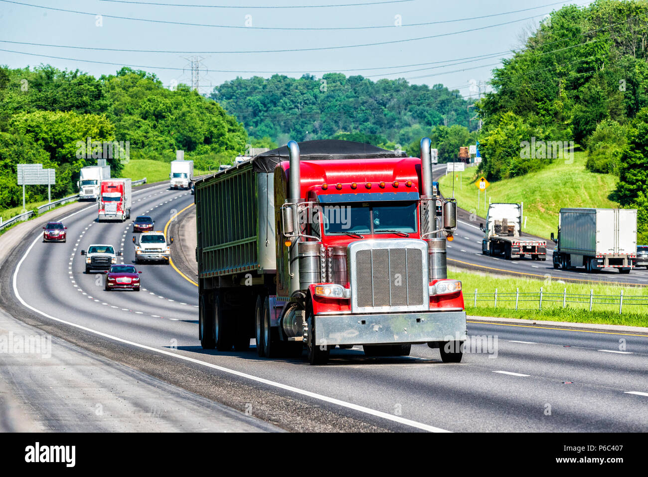 A heavily-loaded 18-wheeler travels the interstate. Note: All logos and identifying marks have been removed from all vehicles.  Image was created on h - Stock Image