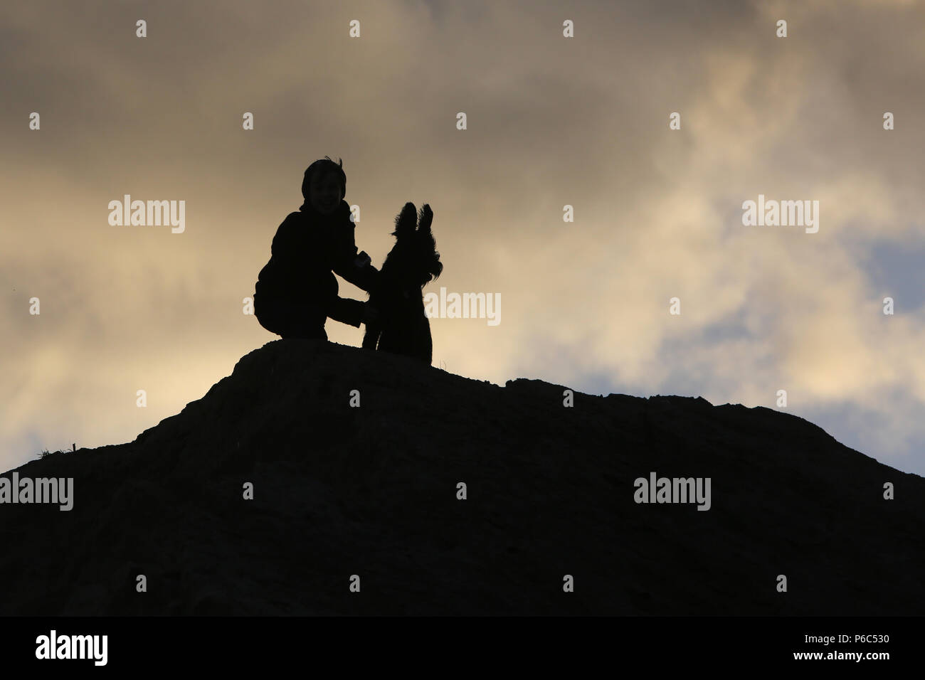 Wustrow, Germany - Silhouette, boy squats with his dog on a dune in the evening - Stock Image