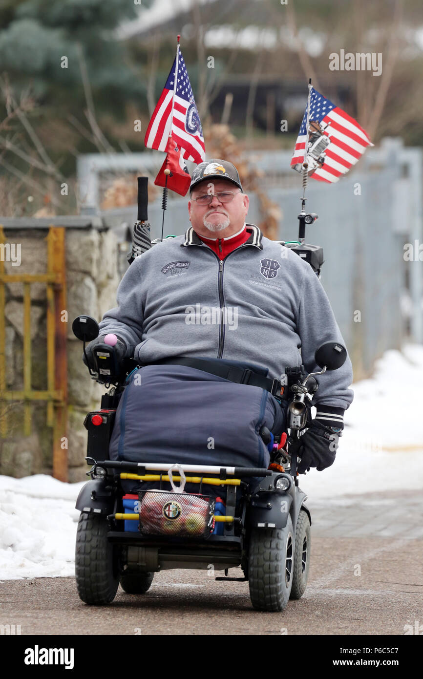 Neuenhagen, man drives his US-flagged electric wheelchair on the day of the swearing-in of US President Donald Trump Stock Photo