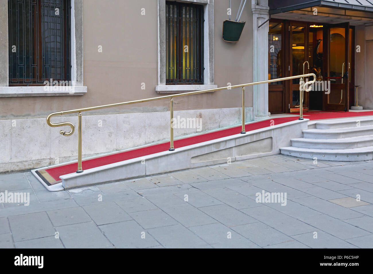 Wheelchair Ramp With Red Carpet for Easy Access in Building - Stock Image