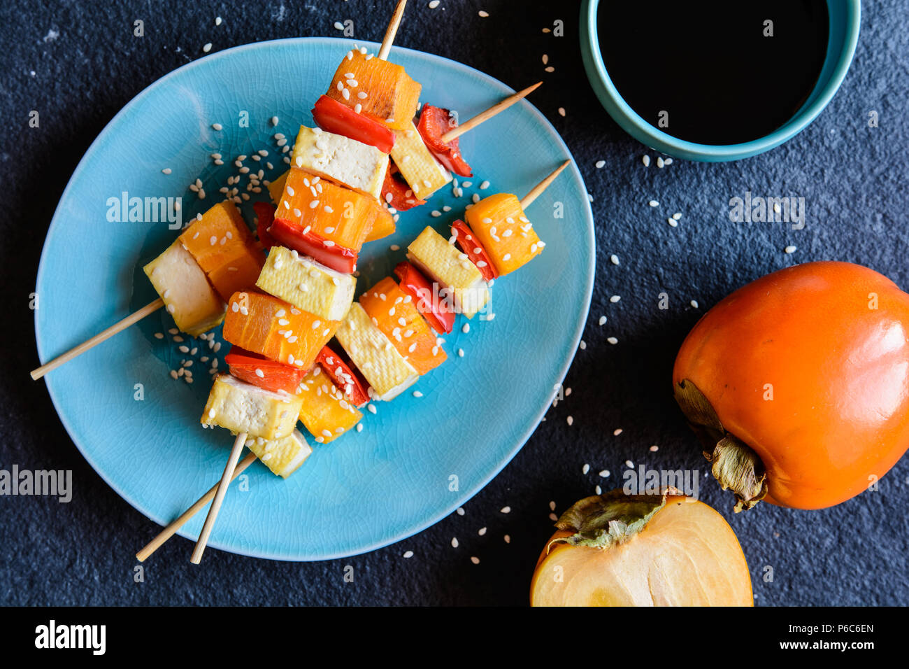 Vegetarian skewers with persimmons, Tofu cheese, red pepper, sesame seeds and served with soya sauce - Stock Image