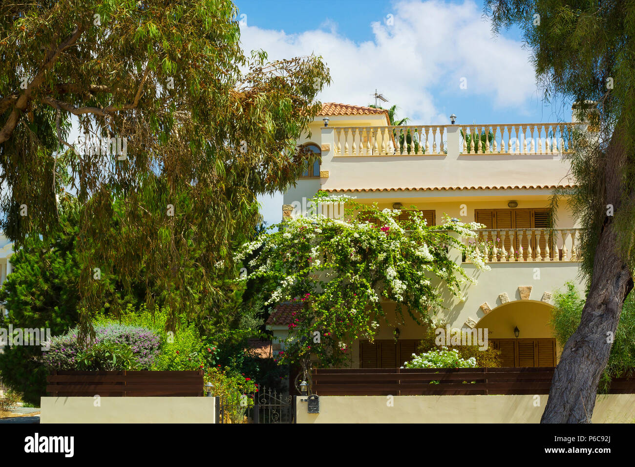 Facade of house with terrace covered with flowering bush and garden around against blue sky Stock Photo